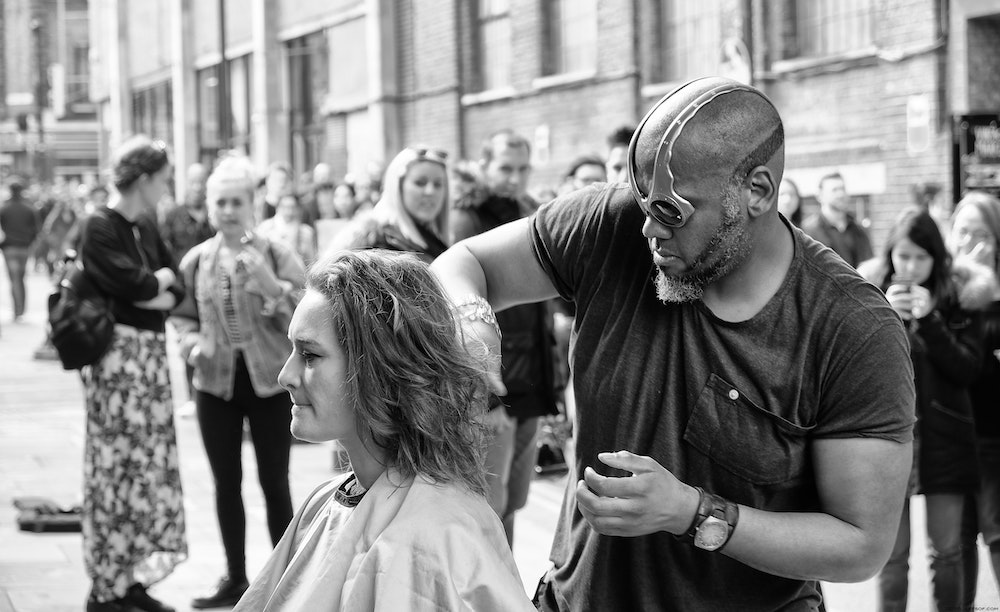 black man cuts white woman's hair in crowded street