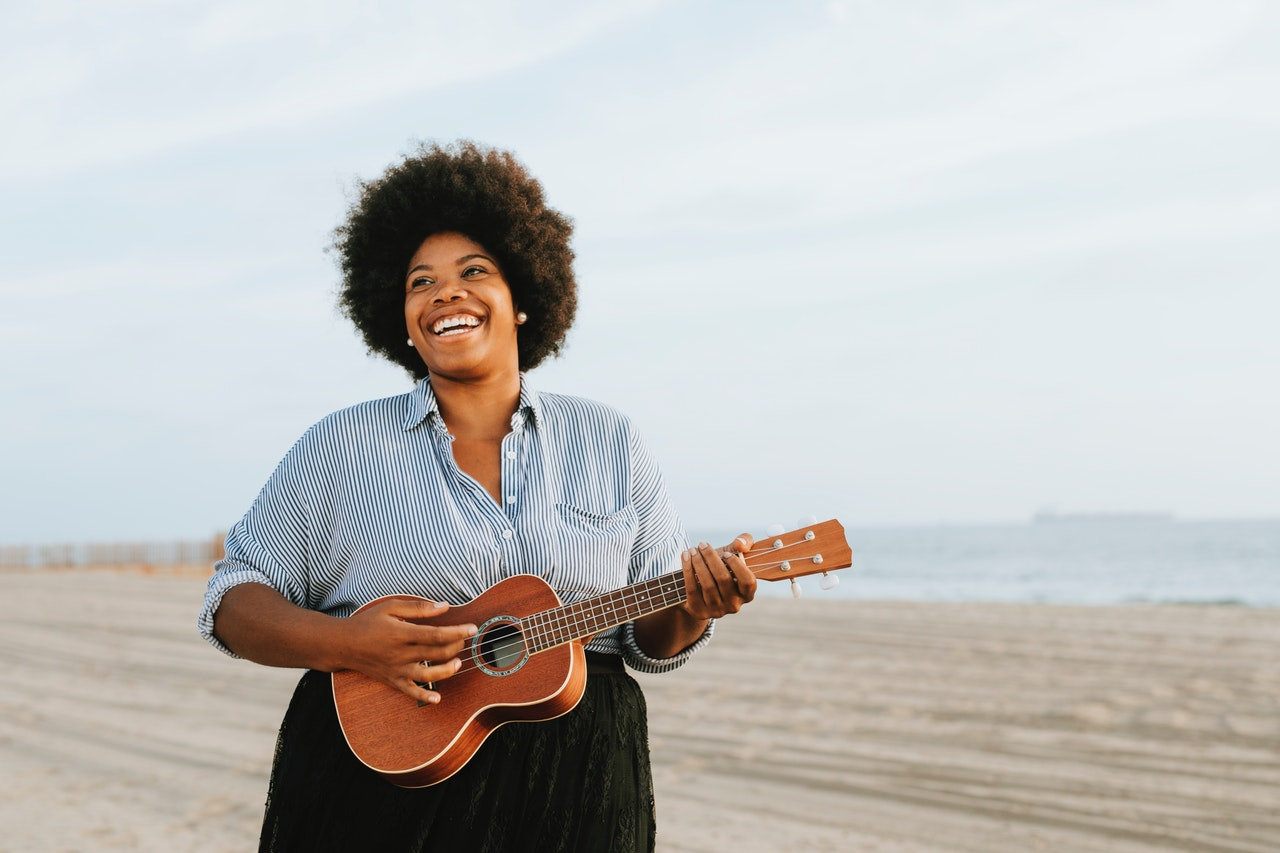 happy woman with ukulele on beach