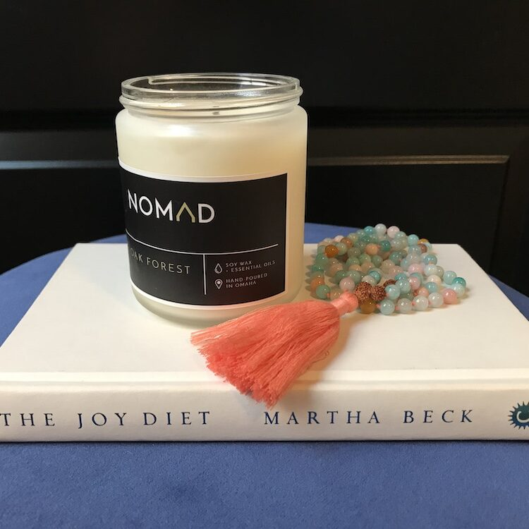 Nomad candle and Mala Collective beads on The Joy Diet book